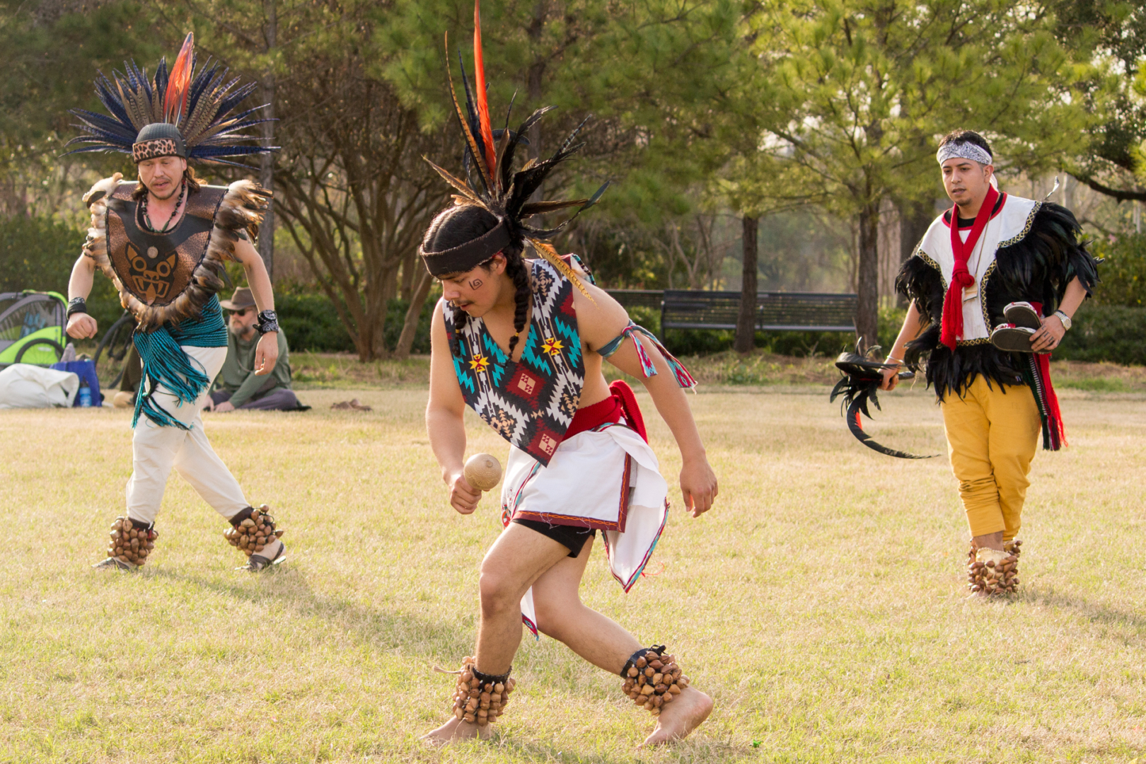 Jesus Navarro (left), Mauricio Turrubiartes III (center) and Uriel Garcia-Vega (right) of the Houston Aztec Dance group partake in a traditional dance ceremony to honor the last Mexica-Aztec tlatoani-leader, Cuauhtémoc. The group meets weekly to learn the Aztec traditions and ceremonies as a way to reconnect with their indigenous heritage. | Katrina Martinez/The Cougar